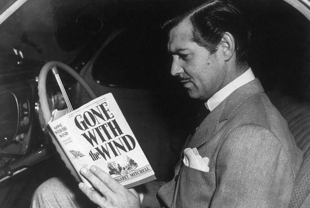 American film star Clark Gable (1901-1960) reading the novel 'Gone With the Wind' by Margaret Mitchell. His greatest role was that of Rhett Butler in the MGM film adaption of the book. (Photo by Hulton Archive/Getty Images)
